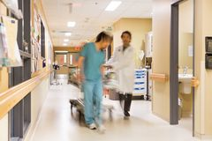 Doctor And Nurse Pulling Stretcher In Hospital Royalty Free Stock Images