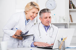 Doctor and nurse reading information. Doctor and nurse check patient data in hospital computer database royalty free stock images