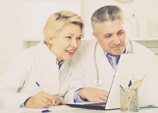 Doctor and nurse reading information. Mature doctor and nurse examine patient data in hospital computer database royalty free stock images