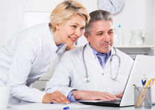 Doctor and nurse reading information. Doctor and nurse reading patient information in hospital computer database royalty free stock images