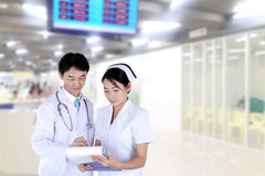 Doctor and nurse reviewing medical chart royalty free stock photography