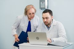 Doctor and nurse reviewing patient information on a laptop computer in an office setting stock photo