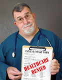 Mature Doctor Displays Healthcare Denied. A doctor or nurse shows a medical form with the words HEALTHCARE DENIED written across it Stock Photo