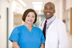 A Doctor And Nurse Standing In A Hospital Corridor. Smiling Royalty Free Stock Photos