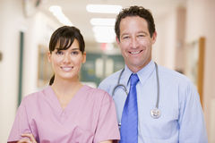 Doctor And Nurse Standing In A Hospital Corridor. Smiling Stock Photo