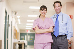 Doctor And Nurse Standing In A Hospital Corridor. Smiling Stock Images