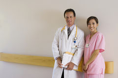 Doctor and nurse standing in hospital corridor, man holding medical file, smiling, portrait Stock Image