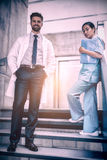 Doctor and nurse standing on staircase Royalty Free Stock Photography