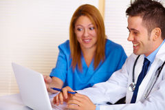 Doctor and a nurse talking. Portrait of a young doctor and a nurse talking and using a laptop on the office Royalty Free Stock Photography