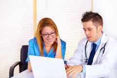 Doctor and a nurse talking. Portrait of a young doctor and a nurse talking and using a laptop on the office Royalty Free Stock Photos