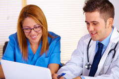 Doctor and a nurse talking. Portrait of a young doctor and a nurse talking and using a laptop on the office Stock Image