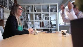 Doctor and nurse talking and laughing while taking coffee stock footage