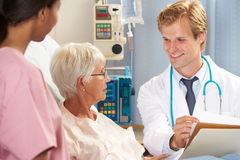 Doctor With Nurse Talking To Senior Female Patient In Bed. Smiling Royalty Free Stock Photos
