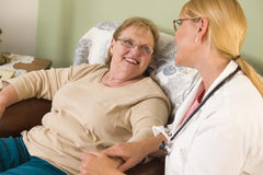 Doctor or Nurse Talking to Sitting Senior Woman Stock Images
