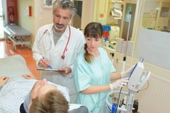 Doctor and nurse telling patient diagnosis. Doctor and nurse telling patient the diagnosis Royalty Free Stock Photos