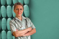 Doctor or nurse in uniform with stethoscope around neck and crossed hands. Happy positive smiled white woman. On cyan drug royalty free stock photography