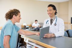 Doctor And Nurse Using Digital Tablet At Hospital Stock Images