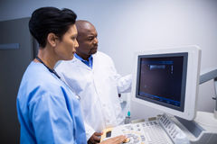 Doctor and nurse using patient monitoring machine in ward Royalty Free Stock Images