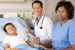 Doctor And Nurse Visiting Child Patient On Ward Stock Image