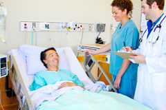 Doctor and nurse visiting with patient Stock Photos
