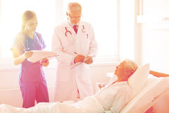 Doctor and nurse visiting senior woman at hospital Stock Photo