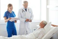 Doctor and nurse visiting senior woman at hospital Royalty Free Stock Photo
