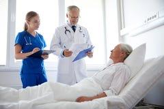Doctor and nurse visiting senior woman at hospital Royalty Free Stock Photos