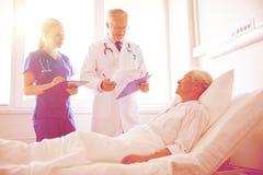 Doctor and nurse visiting senior woman at hospital Royalty Free Stock Image