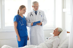 Doctor and nurse visiting senior woman at hospital Stock Image