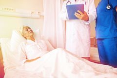 Doctor and nurse visiting senior woman at hospital Stock Images