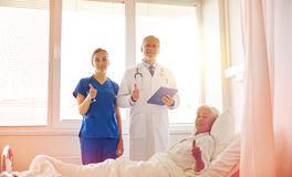 Doctor and nurse visiting senior woman at hospital Royalty Free Stock Photography