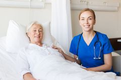 Doctor or nurse visiting senior woman at hospital Stock Image