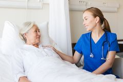 Doctor or nurse visiting senior woman at hospital Stock Photos
