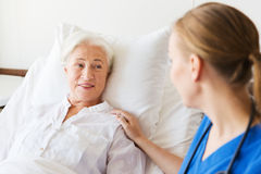 Doctor or nurse visiting senior woman at hospital. Medicine, age, support, health care and people concept - doctor or nurse visiting and cheering senior women Stock Photo
