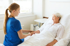 Doctor or nurse visiting senior woman at hospital stock images