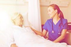Doctor or nurse visiting senior woman at hospital Stock Photos