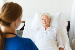 Doctor or nurse visiting senior woman at hospital Royalty Free Stock Images