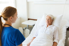 Doctor or nurse visiting senior woman at hospital. Medicine, age, support, health care and people concept - doctor or nurse visiting senior women lying in bed at Stock Photo