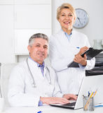 Doctor and nurse waiting for patients. Doctor and nurse in white medical gown waiting for visit patients at table stock photos
