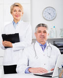 Doctor and nurse waiting for patients. Doctor and nurse in white medical gown waiting for visit patients at table royalty free stock photography