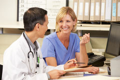 Doctor With Nurse Working At Nurses Station Royalty Free Stock Photography