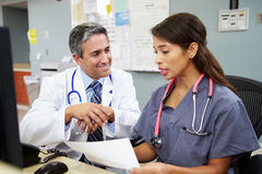 Doctor With Nurse Working At Nurses Station Stock Photo