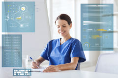 Doctor or nurse writing on clipboard at hospital. Medicine, healthcare, technology and people concept - happy female doctor or nurse with clipboard writing Royalty Free Stock Images