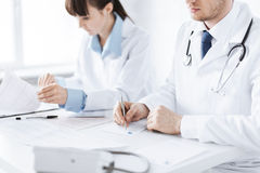 Doctor and nurse writing prescription paper. Picture of doctor and nurse writing prescription paper Royalty Free Stock Image