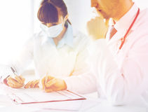 Doctor and nurse writing prescription paper stock image