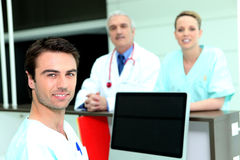 Doctor and nurses around a computer Royalty Free Stock Photos