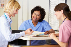 Doctor And Nurses In Discussion At Nurses Station royalty free stock photography