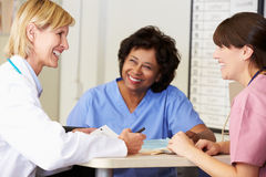 Doctor And Nurses In Discussion At Nurses Station Stock Photo
