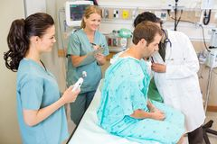 Doctor And Nurses Examining Patient Stock Image
