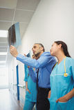 Doctor and nurses looking at x-ray Stock Photos